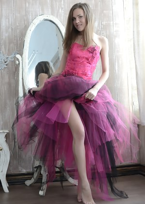 Gorgeous teen cutie stripping an evening dress and showing body in front of a big mirror.