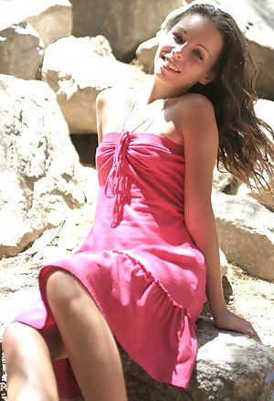 Sexy teen sits out on some rocks in the shadows in her pink prom like dress so sexy