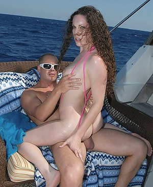 Wonderful brunette having curly hair is enjoying fantastic threesome with two busty men. She just can't stop sucking and riding their cocks.