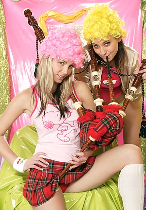 Two lesbian teen girls blowing on their scottish bagpipes