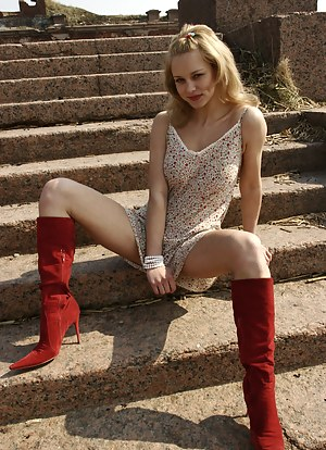 Startling blonde kitten in red high-heeled boots demonstrates her nude body on the age-old stone steps in a desert place.