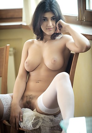 Seductive brunette poses in white stockings showing off her perfect big tits and sweet twat.