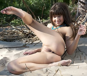 Fascinating dark haired teen honey with blue beads around her neck posing naked outdoor.